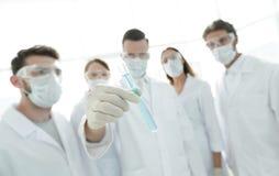 背景图象是一个小组医护人员与液体一起使用在实验室 库存照片