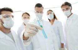 背景图象是一个小组医护人员与液体一起使用在实验室 免版税库存图片