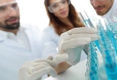 背景图象是学习在玻璃管的一个小组科学家液体 免版税库存图片