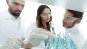 背景图象是学习在玻璃管的一个小组科学家液体 图库摄影