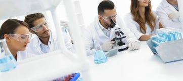背景图象是工作在实验室里的一个小组科学家 免版税库存照片