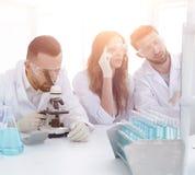 背景图象是工作在laborat的一个小组科学家 免版税库存图片