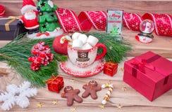 背景圣诞节关闭红色时间 一个杯子用在一张木桌上的雪人、蛋白软糖和姜饼曲奇饼用圣诞装饰装饰 免版税库存图片
