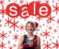 背景圣诞节女孩愉快的销售额购物白色 圣诞老人帽子的美丽的妇女拿着圣诞节礼物 免版税库存照片