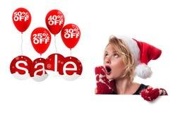 背景圣诞节女孩愉快的销售额购物白色 圣诞老人帽子的美丽的妇女拿着圣诞节礼物 免版税库存图片
