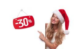 背景圣诞节女孩愉快的销售额购物白色 圣诞老人帽子的美丽的妇女指向销售的 库存照片