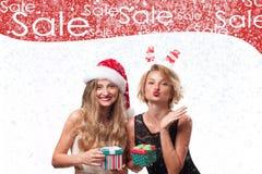 背景圣诞节女孩愉快的销售额购物白色 拿着圣诞节礼物的美丽的womanin圣诞老人帽子 库存图片