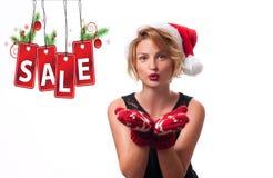 背景圣诞节女孩愉快的销售额购物白色 美丽的womanin圣诞老人帽子和手套 免版税库存图片