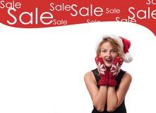 背景圣诞节女孩愉快的销售额购物白色 美丽的womanin圣诞老人帽子和手套 免版税库存照片