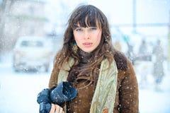 背景圣诞节女孩愉快的销售额购物白色 美丽的惊奇的妇女在冬天在手中穿衣有照相机与雪的冬天背景,情感 画象  库存图片