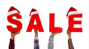 背景圣诞节女孩愉快的销售额购物白色 的手拿着与词销售的卡片与圣诞老人上面帽子前面 免版税库存图片