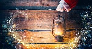 背景圣诞节构成的节假日场面 拿着葡萄酒油灯的圣诞老人手 免版税库存照片