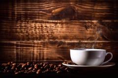背景在一个杯子的咖啡饮料用在木纹理的咖啡豆 免版税图库摄影