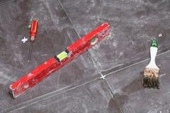 背景在家铺磁砖砖地粘合剂的建筑画笔 免版税库存图片