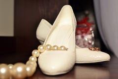 背景在新娘的鞋子的婚戒 免版税库存图片