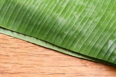 背景在木地板上的香蕉叶子 免版税库存图片