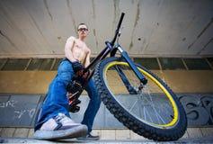 背景在都市年轻人的自行车人 免版税库存照片