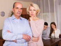 背景夫妇与年长的人离婚查出在哀伤的白色 免版税库存照片