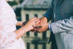 背景夫妇递她的藏品结婚显示那里水婚礼妻子的环形 免版税库存照片