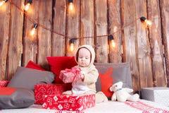 背景对光检查圣诞节构成黑暗的夜间新的s玩具年 小女孩开会和解开礼物 工作服驯鹿服装 免版税库存照片