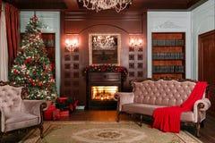 背景对光检查圣诞节构成黑暗的夜间新的s玩具年 与一盏白色壁炉、装饰的树、沙发、大窗口和枝形吊灯的经典公寓 图库摄影