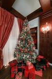 背景对光检查圣诞节构成黑暗的夜间新的s玩具年 与一盏白色壁炉、装饰的树、沙发、大窗口和枝形吊灯的经典公寓 免版税库存图片