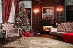 背景对光检查圣诞节构成黑暗的夜间新的s玩具年 与一盏白色壁炉、装饰的树、沙发、大窗口和枝形吊灯的经典公寓 免版税库存照片