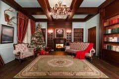 背景对光检查圣诞节构成黑暗的夜间新的s玩具年 与一盏白色壁炉、装饰的树、沙发、大窗口和枝形吊灯的经典公寓 免版税图库摄影