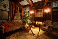 背景对光检查圣诞节构成黑暗的夜间新的s玩具年 经典公寓的年轻美丽的白肤金发的妇女一个白色壁炉,装饰的树 免版税库存照片