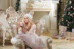 背景对光检查圣诞节构成黑暗的夜间新的s玩具年 有咖啡的年轻美丽的白肤金发的妇女在经典公寓的一个白色壁炉,装饰 库存照片