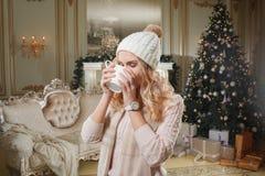 背景对光检查圣诞节构成黑暗的夜间新的s玩具年 有咖啡的年轻美丽的白肤金发的妇女在经典公寓的一个白色壁炉,装饰 免版税库存图片
