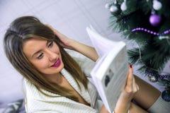 背景对光检查圣诞节构成黑暗的夜间新的s玩具年 年轻美丽的深色的妇女读了在经典公寓的书,装饰的树 免版税库存照片