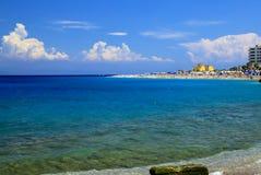 背景峡湾光芒海运星期日 美丽如画的夏天海滩,在海浪线的小卵石在美丽的绿松石海,罗得岛,Greee 免版税库存图片