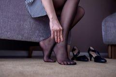 背景弄脏了关心概念表面健康防护屏蔽的药片 遭受在脚腕的痛苦的女商人 库存图片