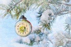 背景新年度 以显示在多雪的杉树的时钟的形式新年玻璃圣诞节玩具除夕, 免版税库存照片
