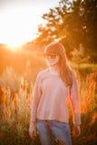 背景日落的年轻现代女孩 免版税库存照片
