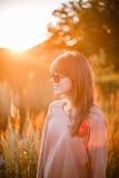 背景日落的年轻现代女孩 库存照片