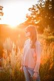 背景日落的年轻现代女孩 免版税库存图片