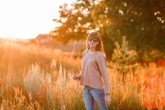 背景日落的年轻现代女孩 图库摄影