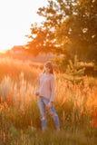 背景日落的年轻现代女孩 库存图片