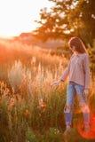 背景日落的年轻现代女孩 免版税图库摄影