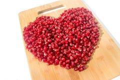 背景果子查出的石榴红色白色 成熟素食食物 甜水多的新有机种子木头背景的心脏 热带健康未加工的特写镜头 图库摄影
