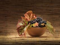 背景柳条碗的葡萄 免版税库存图片