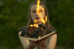 背景棒万圣节月光附注 女孩拿着一本灼烧的书以森林为背景 库存照片