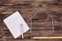 背景概念家房子查出在白色 在一个工作表上的木式样房子与工具和倒空螺纹笔记本 免版税库存图片