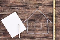 背景概念家房子查出在白色 在一个工作表上的木式样房子与工具和倒空螺纹笔记本 图库摄影