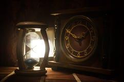 背景概念查出的目的程序时间白色 滴漏时钟和老葡萄酒木时钟剪影有箭头的和烟在黑暗的背景与热的黄色ora 库存图片
