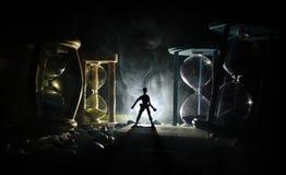 背景概念查出的目的程序时间白色 站立在有烟的在黑暗的背景的滴漏和光之间的一个人的剪影 免版税库存图片