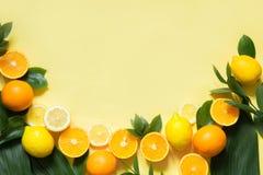 背景概念框架沙子贝壳夏天 套热带水果、柠檬、桔子和绿色在黄色离开 复制空间并且从上面观看 免版税库存照片