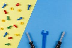 背景模板文本玩具 孩子建筑戏弄在蓝色和黄色背景的工具 顶视图 图库摄影
